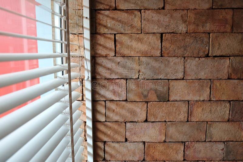 Muro di mattoni e luce dell'ombra dalla tenda fotografie stock libere da diritti