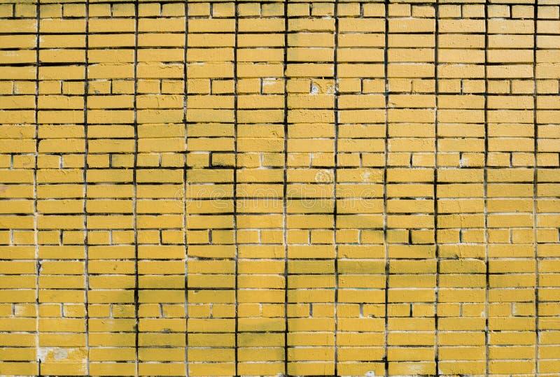 Muro di mattoni giallo con le tracce di pittura bianca fotografia stock libera da diritti