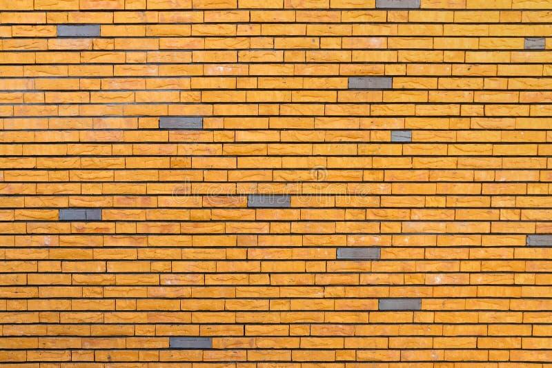Muro di mattoni giallo sparpagliato con alcuni mattoni grigi immagine stock