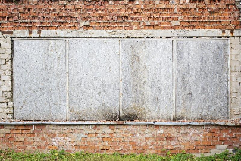 Muro di mattoni incrinato abbandonato di lerciume con imbarcato sulle finestre fotografie stock