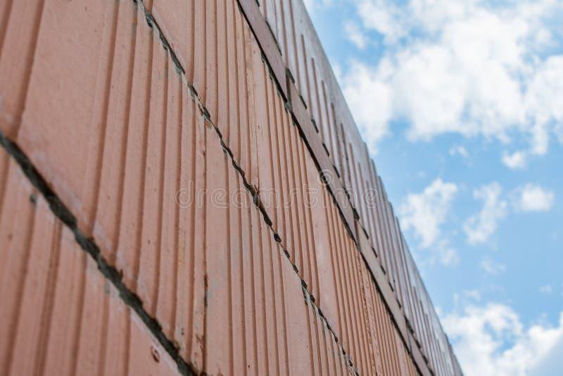 Muro di mattoni rosso sui precedenti del cielo blu fotografie stock