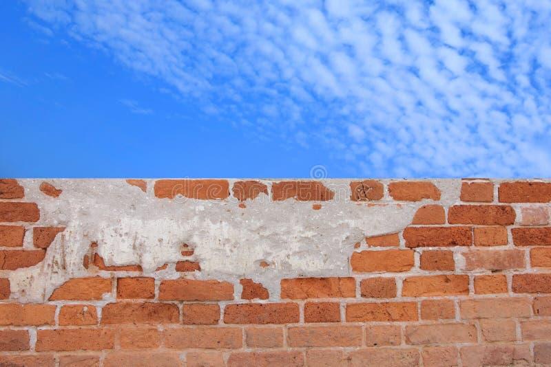 Muro di mattoni sotto un cielo blu nuvoloso fotografia stock