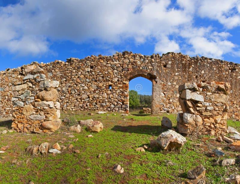 Muro di pietra leggera con passaggio aracchito, piccole colonne rovinate nel campo verde fotografia stock