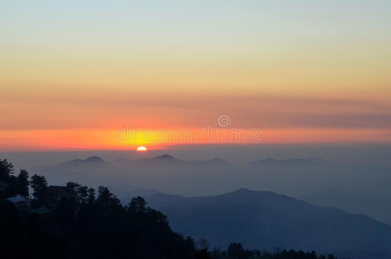 Sunset over mountains and trees of Murree Punjab Pakistan. Murree, Pakistan - January 15, 2018: A sunset over the pine trees and hills of Murree town in northern royalty free stock photos