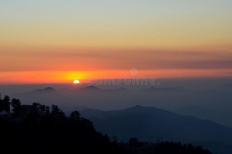 Sunset over mountains and trees of Murree Punjab Pakistan. Murree, Pakistan - January 15, 2018: A sunset over the pine trees and hills of Murree town in northern royalty free stock photo