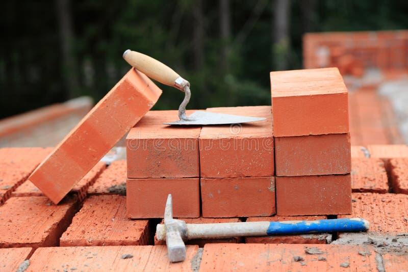Murslev och hammare på tegelstenarna arkivfoton