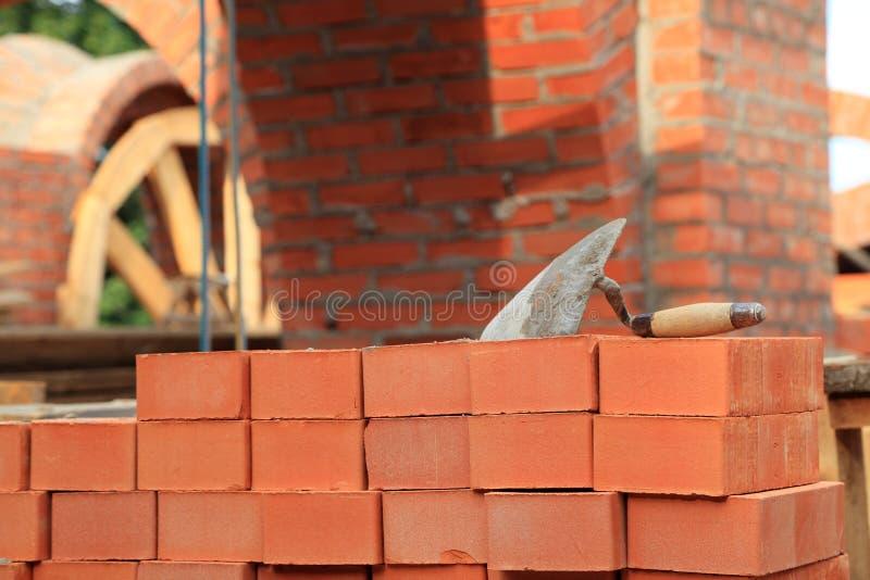 Murslev och hammare på tegelstenarna arkivfoto