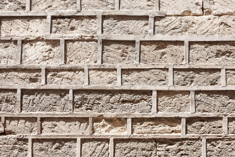 Murverk av forntida en eroderad stenvägg arkivfoto