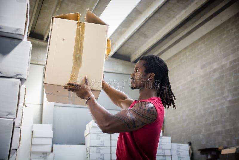 Murzyn pracuje w magazynie, rusza się pudełka fotografia stock