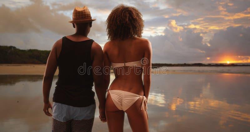 Murzyna i kobiety chwyta ręki podczas gdy przyglądający przy malowniczym horyzontem i zmierzchem out obrazy stock