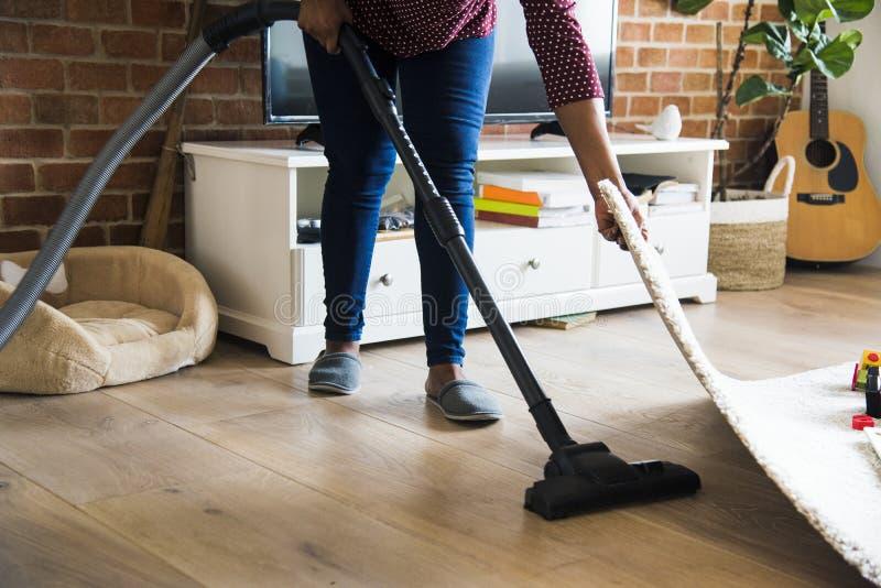 Murzynka jest cleaning pokojem z próżnią zdjęcie royalty free