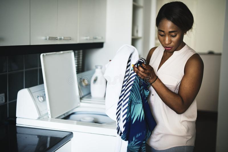 Murzynka używa pralkę robi pralni zdjęcie stock