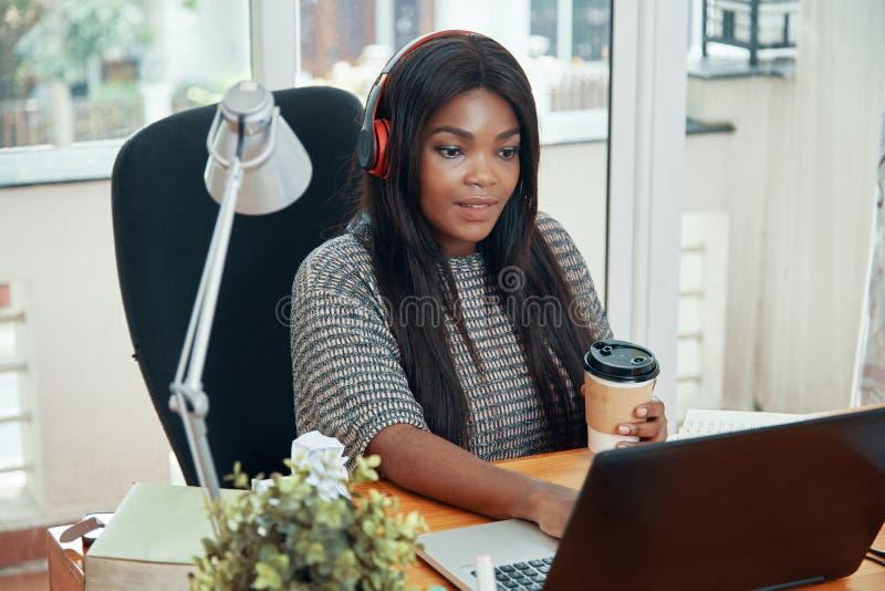 Murzynka w hełmofonach pracuje na laptopie zdjęcia royalty free