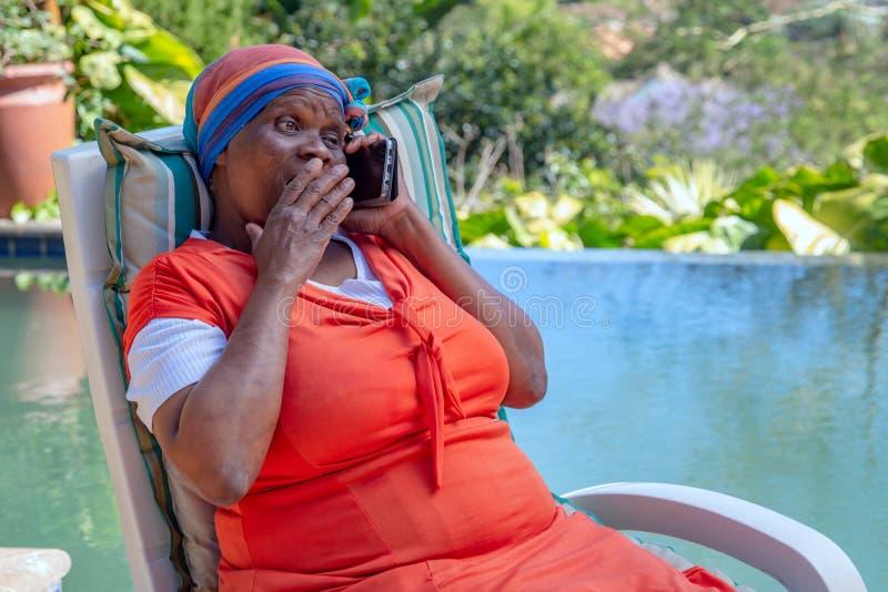 Murzynka z zdziwionym wyrażeniem na jej twarzy i trzymać jej rękę jej usta podczas gdy opowiadający na telefonie komórkowym obrazy royalty free