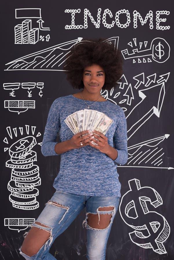 Murzynki mienia pieniądze na szarym tle fotografia royalty free