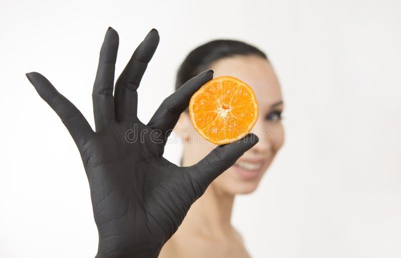Murzynki ręki mienia pomarańczowe połówki blisko ona twarz Czarna ręka z jaskrawą smakowitą mandarynką obraz stock