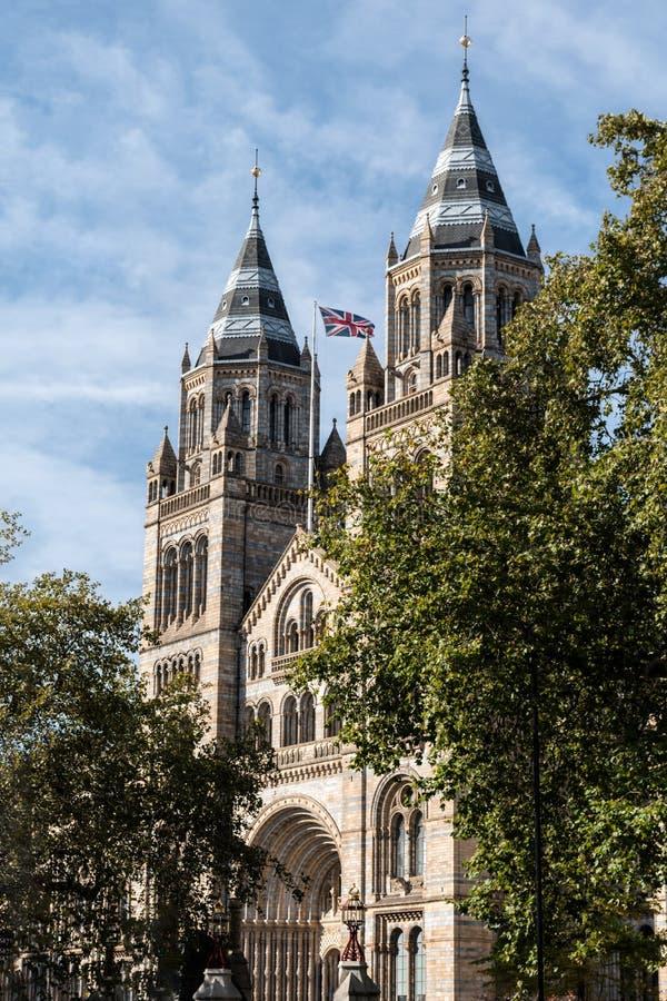 Musée d'histoire naturelle de Londres, Royaume-Uni avec le drapeau britannique un jour ensoleillé image libre de droits