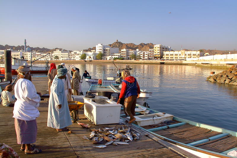 MUSCAT, ΟΜΑΝ - 11 ΦΕΒΡΟΥΑΡΊΟΥ 2012: Ο ψαράς στα ψάρια Muttrah ελλιμενίζει τα ξημερώματα με Muttrah corniche στο υπόβαθρο στοκ φωτογραφία