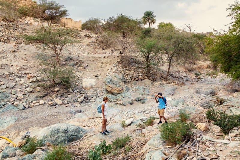 Muscat, Omán - 16 de diciembre de 2018: los turistas toman imágenes en el lecho de un río seco - cauce del río seco - en las cerc fotografía de archivo libre de regalías