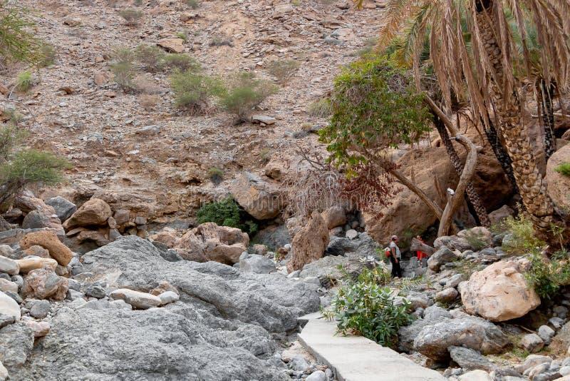 Muscat Oman - December 16, 2018: gruppen av turister promenerar wadin - en torkad övre flodbädd - i utkanten av Muscat royaltyfri fotografi