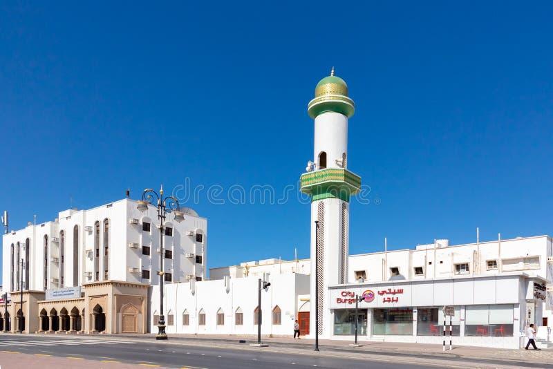 Muscat Oman - December 17, 2018: minaret ?ver hus p? en stadsgata royaltyfria bilder