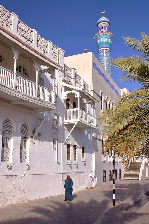 MUSCAT OMAN - FEBRUARI 10, 2012: En omansk man som promenerar Sur Al Lewatia Mosque i Muttrah royaltyfri fotografi