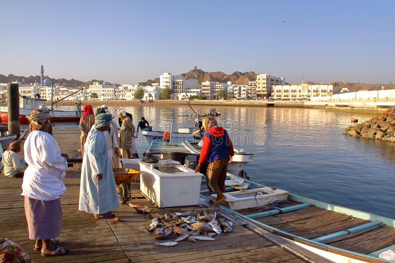 MUSCAT OMAN - FEBRUARI 11, 2012: Fiskaren på den Muttrah fisken ansluter otta med Muttrah corniche i bakgrunden arkivbild
