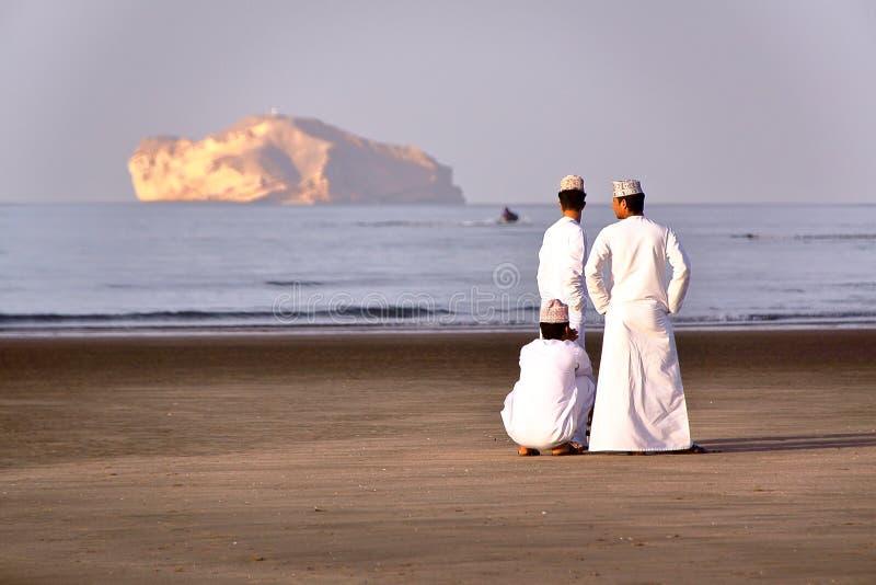 MUSCAT OMAN - FEBRUARI 9, 2012: Tre omanska män klädde traditionellt på den huvudsakliga stranden i centrala Muscat arkivfoto