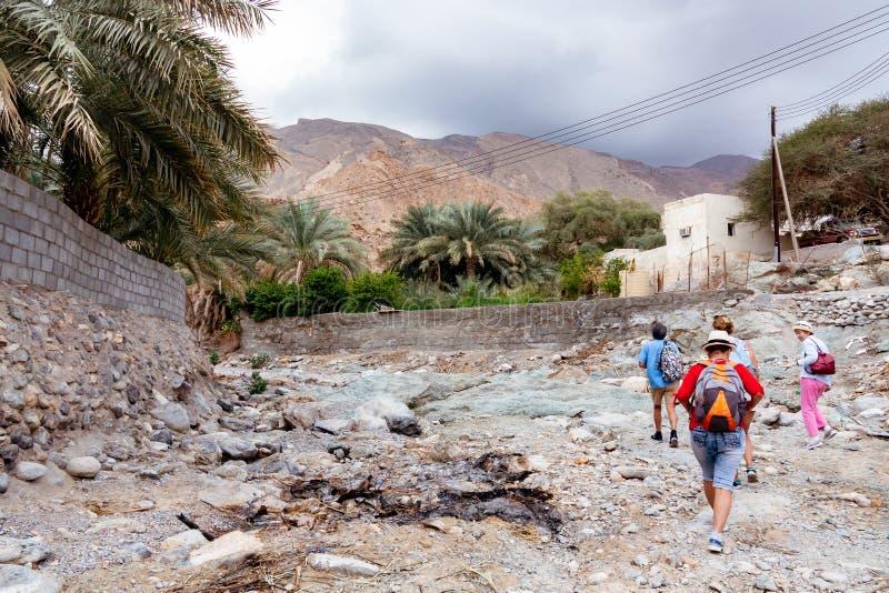 Muscateldruif, Oman - December 16, 2018: de groep toeristen loopt langs de wadi - een opgedroogd rivierbed - in de rand van Musca royalty-vrije stock fotografie