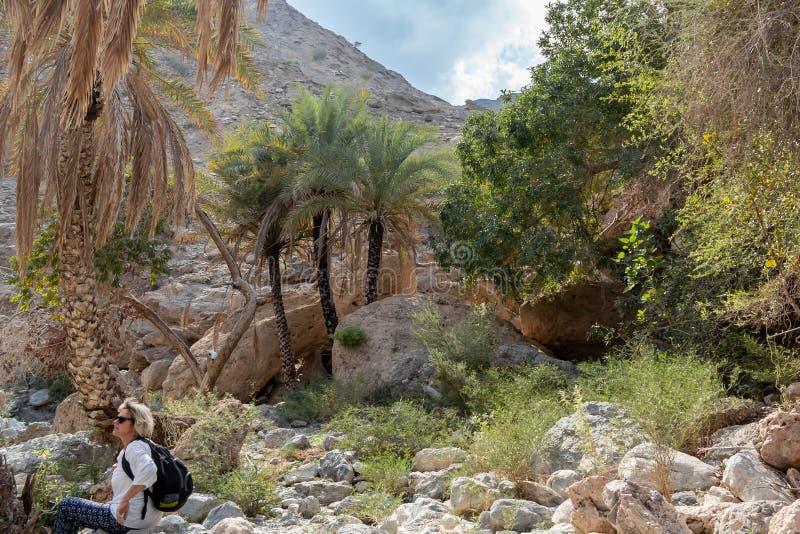 Muscateldruif, Oman - December 16, 2018: de vrouwelijke toerist loopt langs de wadi - een opgedroogd rivierbed - in de rand van M royalty-vrije stock afbeelding