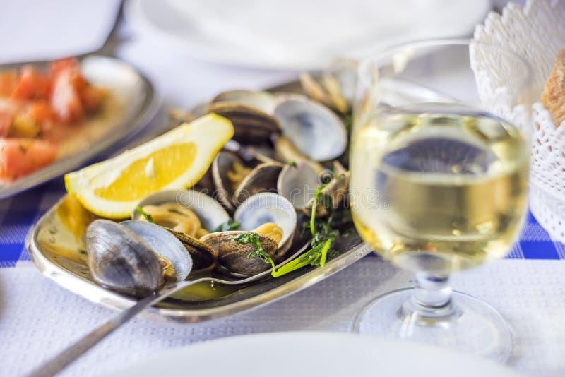 Muscheln gedient auf Tafelsilber mit Weißwein stockfotos