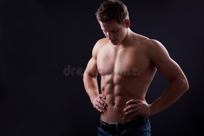 Muscle сексуальный нагой молодой человек представляя в джинсах стоковое изображение rf