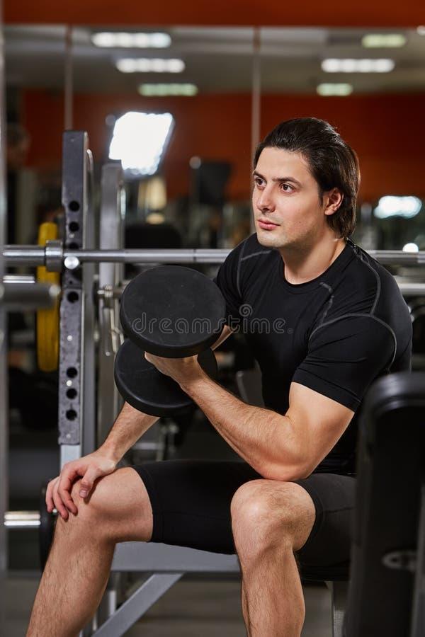 Muscle al varón en el sportwear negro que trabaja con pesas de gimnasia en gimnasio contra el espejo imagen de archivo libre de regalías