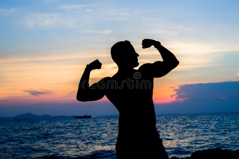 Muscle on the beach Silhouette on sunset royalty free stock photos
