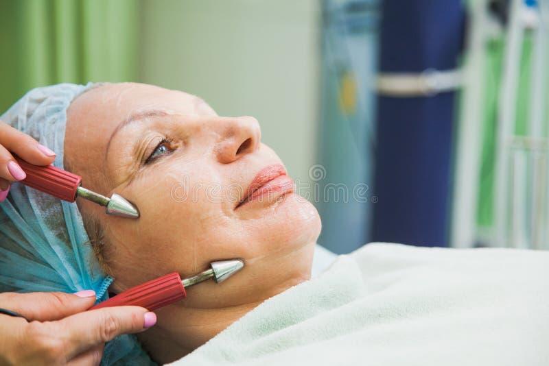 Muscle en modifiant la tonalité la procédure pour la femme supérieure dans la clinique de cosmétologie images stock