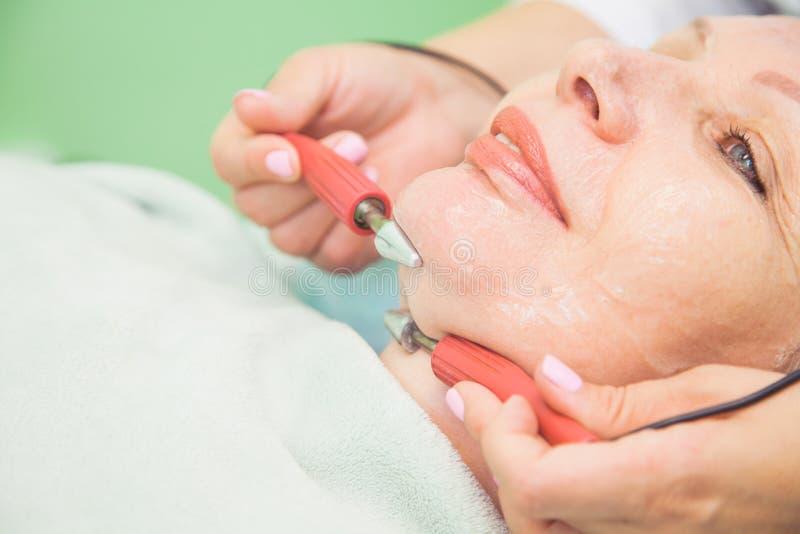Muscle en modifiant la tonalité la procédure pour la femme supérieure dans la clinique de cosmétologie image stock