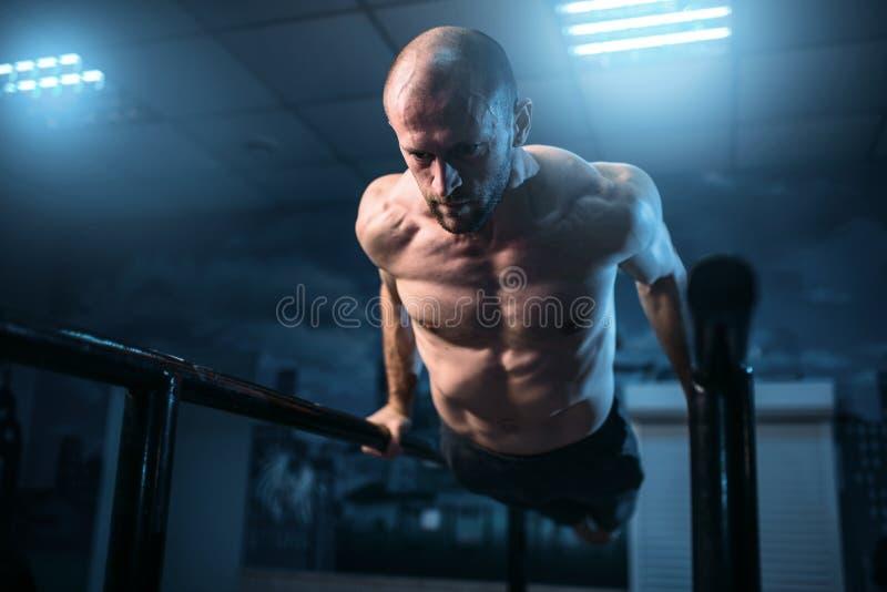 Muscle exercícios da ginasta em barras de esportes no gym fotos de stock