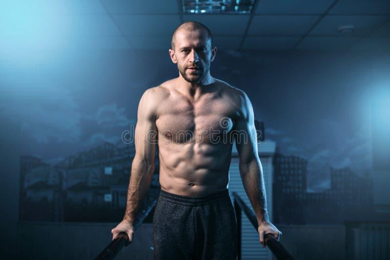 Muscle exercícios da ginasta em barras de esportes no gym fotos de stock royalty free