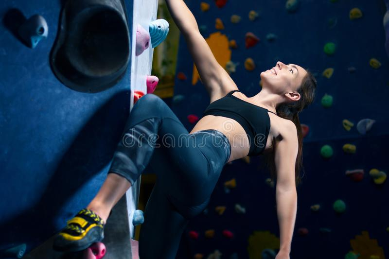 Muscle female woman climbing bouldering in training hall stock photography