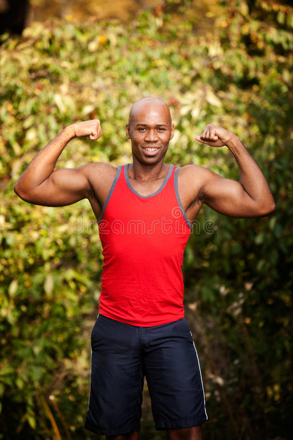 Muscle Fitness. A male flexing his biceps - isolated against a green royalty free stock photos