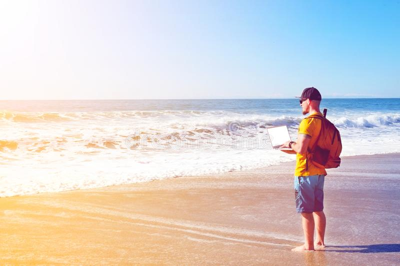 Muscle guy wearing surfer outfit, blue shorts and yellow t-shirt, working on holiday with laptop on an empty beach stock photos
