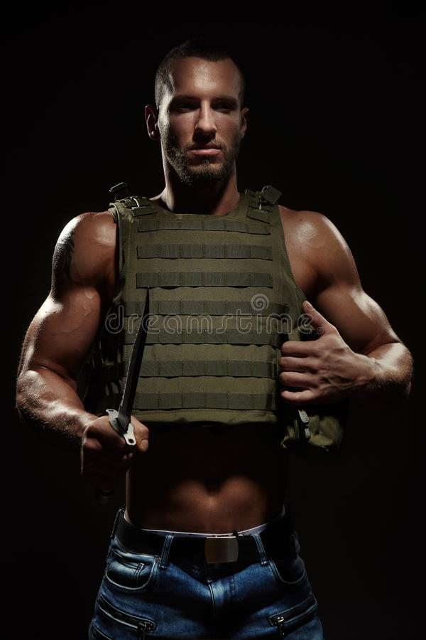 Military style muscle man in tactical vest posing with survival knife royalty free stock photos
