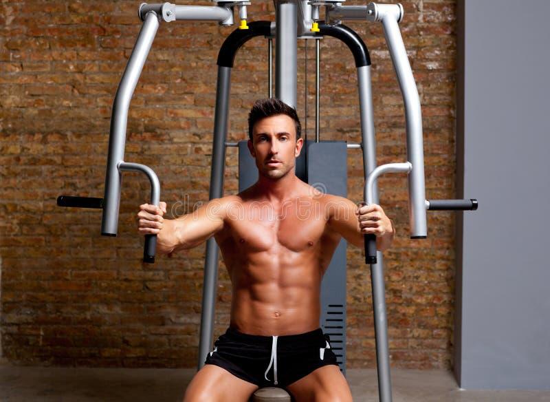 Muscle l'exercice d'homme sur le club de forme physique de gymnastique de sport photo libre de droits