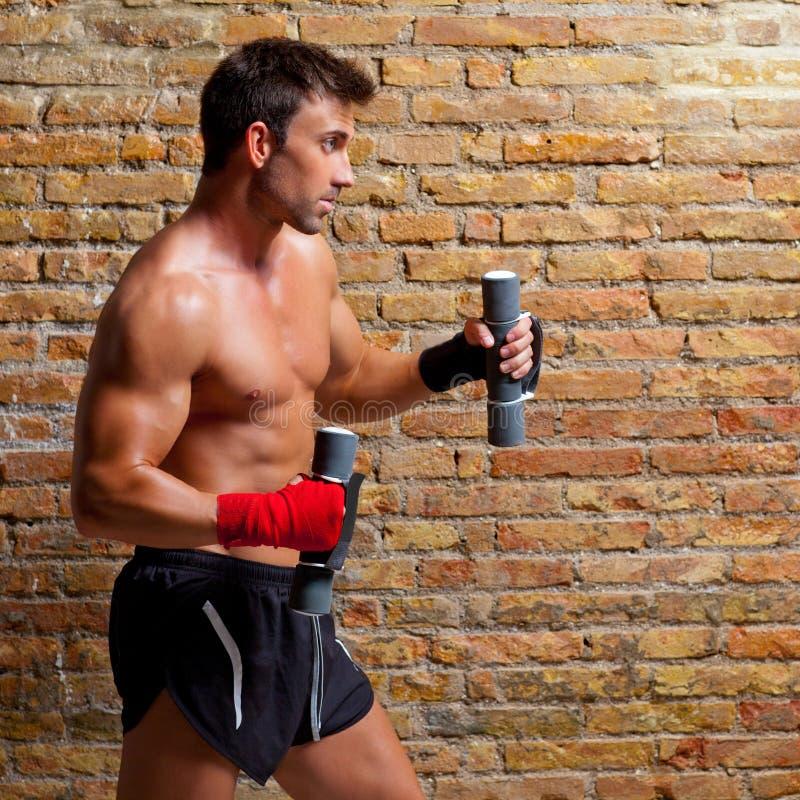 Muscle l'uomo del pugile con la fasciatura ed i pesi del pugno fotografia stock libera da diritti