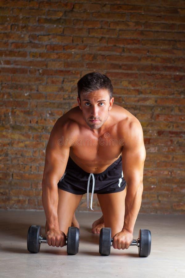 Muscle l'uomo a forma di sulle ginocchia con i pesi di addestramento immagine stock
