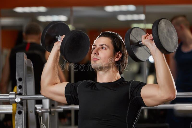 Muscle le mâle dans le sportwear noir fonctionnant avec des haltères dans le gymnase contre le miroir photographie stock libre de droits