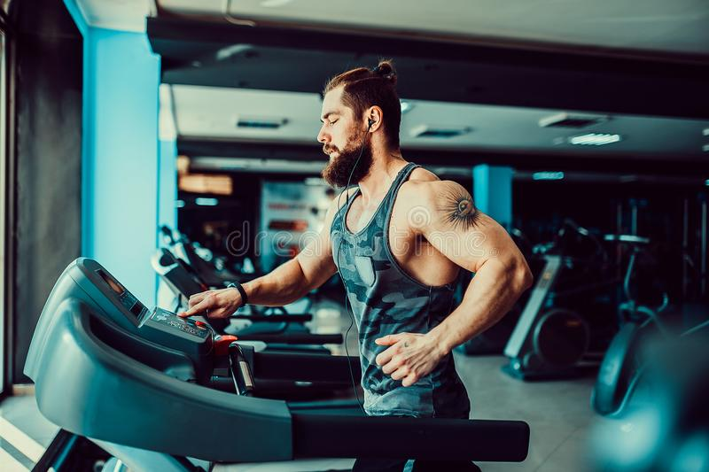 Muscle man running on treadmill. Fit Muscle Bearded Man With Headphones Running on Treadmill in Gym royalty free stock photos