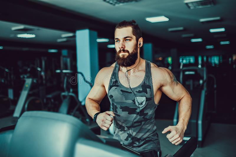 Muscle man running on treadmill. Fit Muscle Bearded Man With Headphones Running on Treadmill in Gym stock images