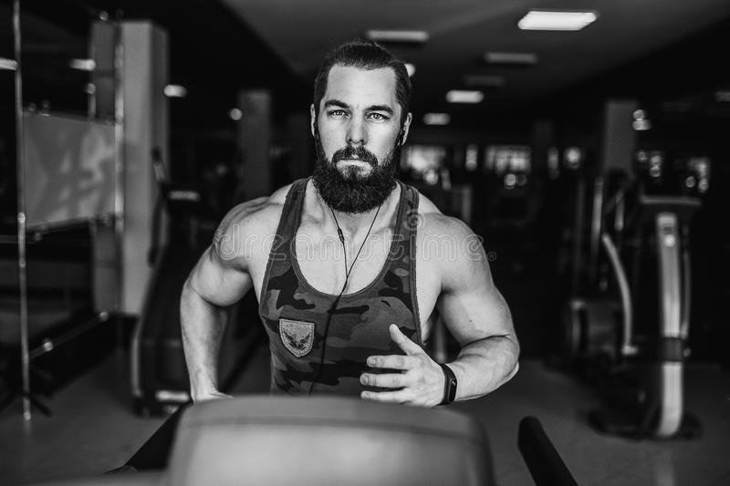 Muscle man running on treadmill. Fit Muscle Bearded Man With Headphones Running on Treadmill in Gym stock photography