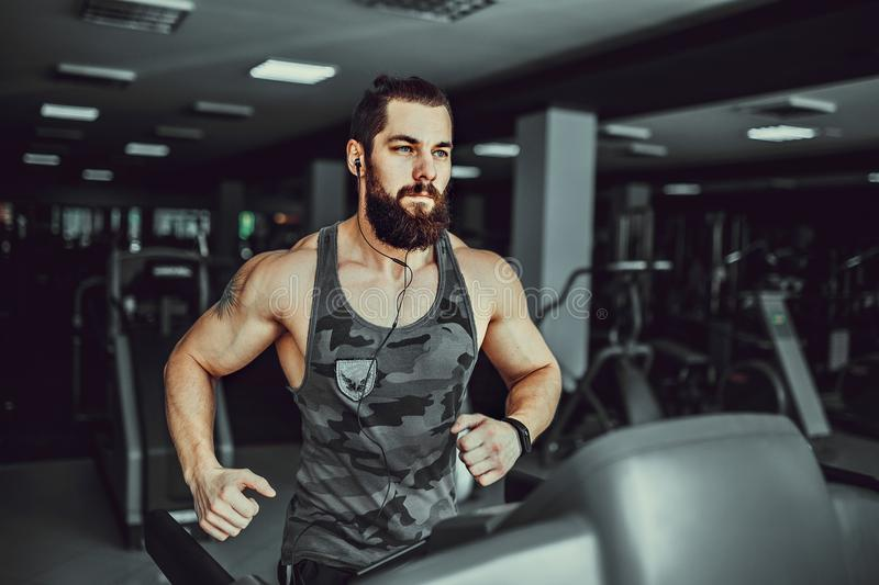 Muscle man running on treadmill. Fit Muscle Bearded Man With Headphones Running on Treadmill in Gym royalty free stock images
